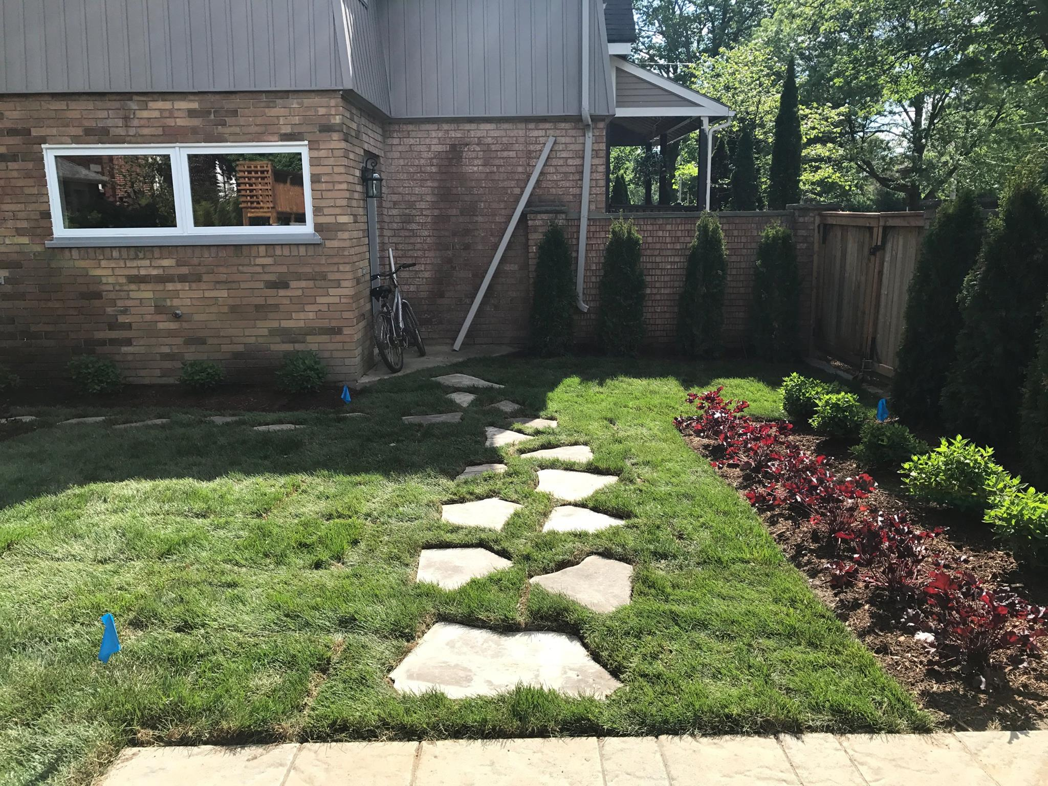 custom stone path with new landscaping grass in backyard